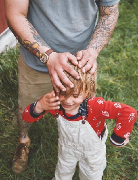 Man wearing Shinola watch playing with his daughter