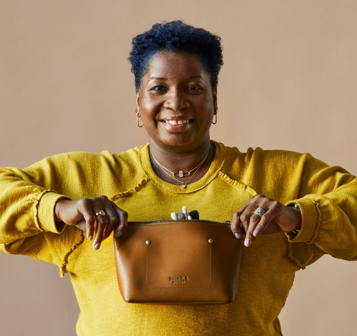 Woman holding a shinola leather pouch