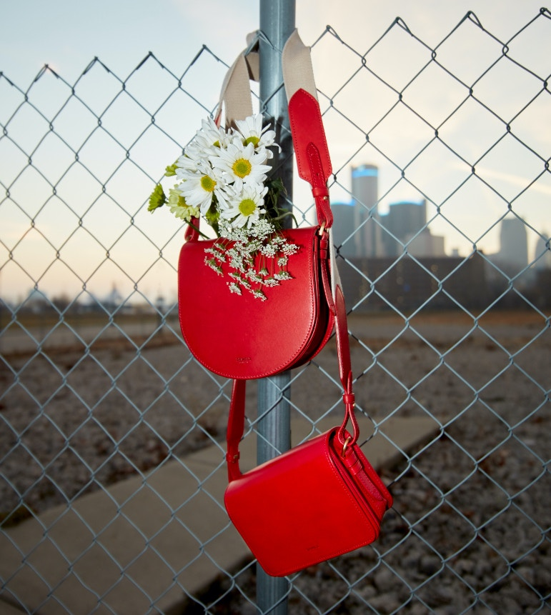red leather bags, with flowers coming out of them, hanging from a fence