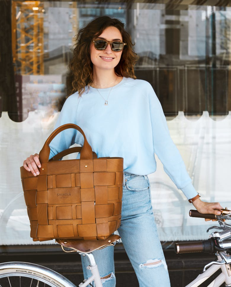 image of woman holding back next to bike