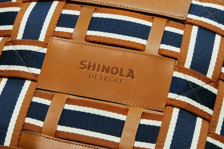 close up shot of leather and brand stripe webbing on bag