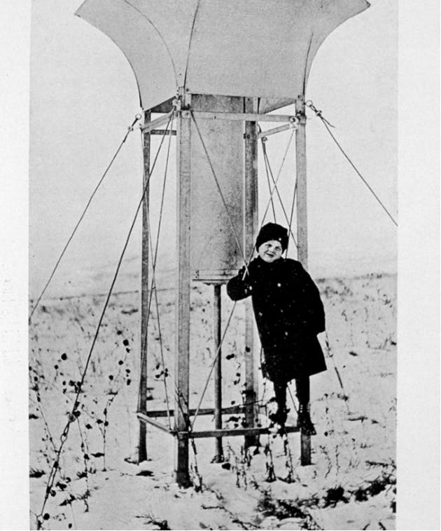old time picture of a kid standing next to snow-guage
