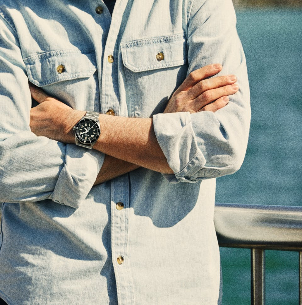 Man standing outside, arms crossed, wearing a Shinola watch