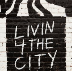 Mural with the words 'LIVIN FOR THE CITY' written, against a cinderblock wall