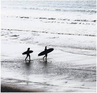 Two people walking along the beach, through ankle-deep surf, with their surfboards tucked under their arms.